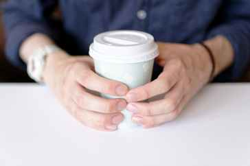 photo of person holding white paper cup