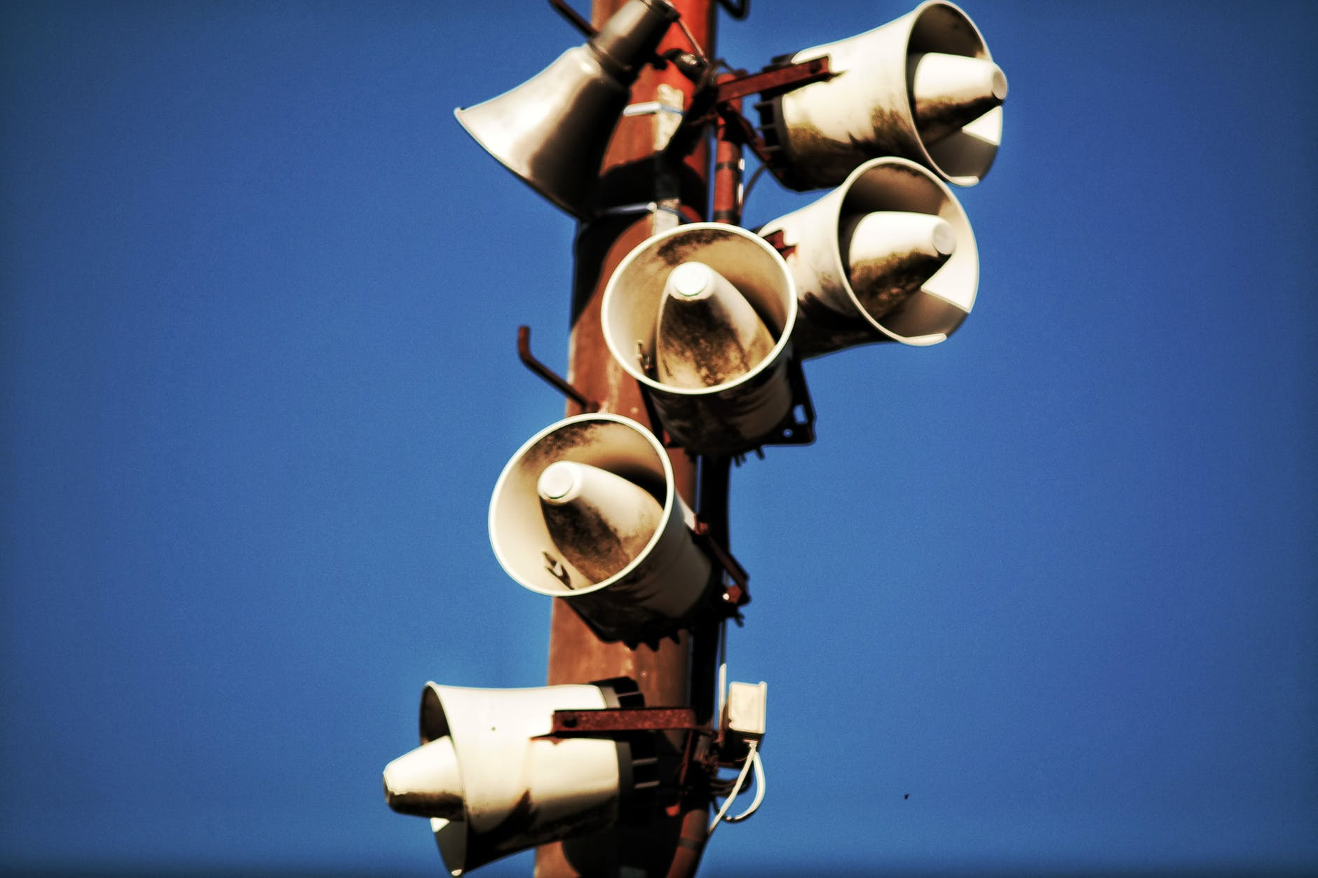 megaphone speakers on wooden post