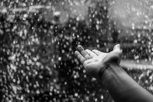 black and white hand raining