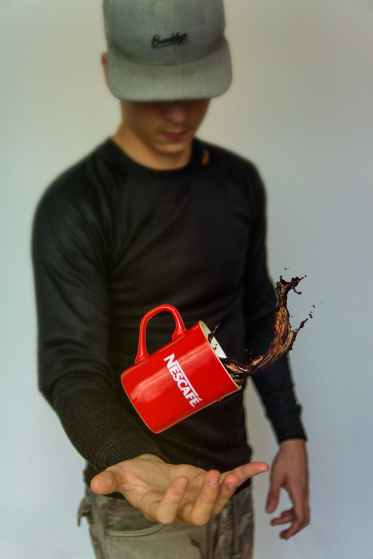 photo of man tossing nescafe mug