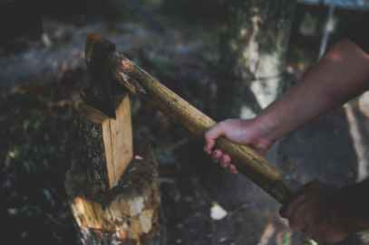a man holds an old worn axe