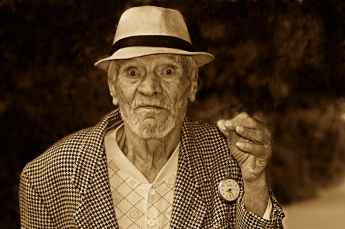 grayscale photo of a man in houndstooth print suit jacket wearing a hat