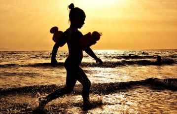 silhouette of girl running on the seashore during golden hour