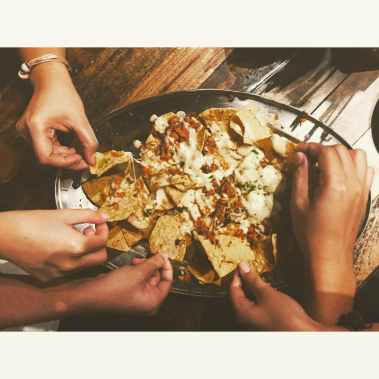 close up photography of people picking nachos chips