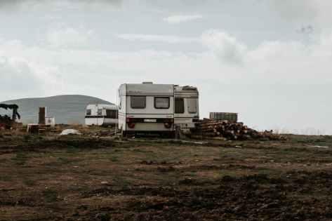 gray camper trailer on grass field