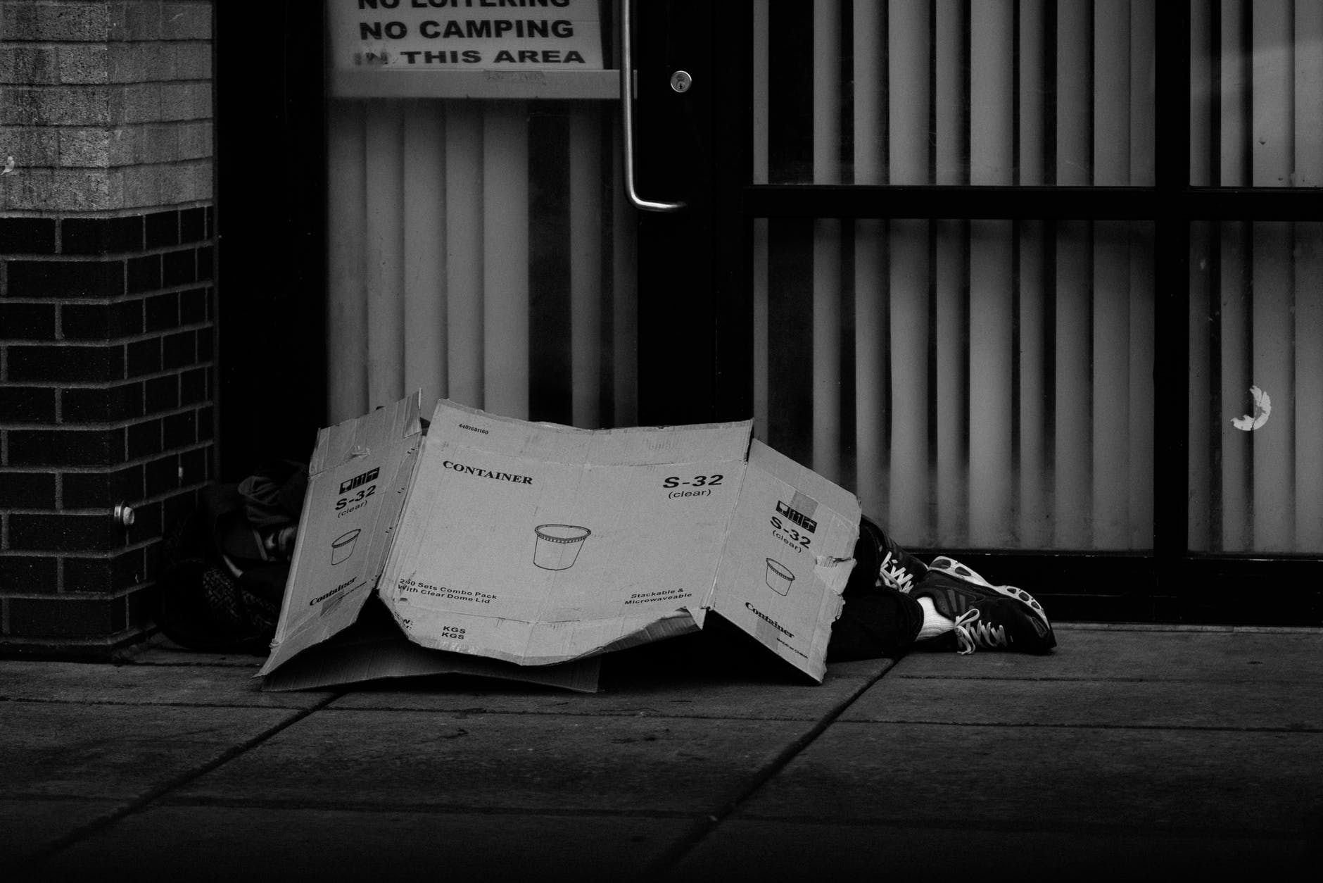 grayscale photo of human lying on ground covered of cardboard box