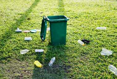 green trash bin on green grass field