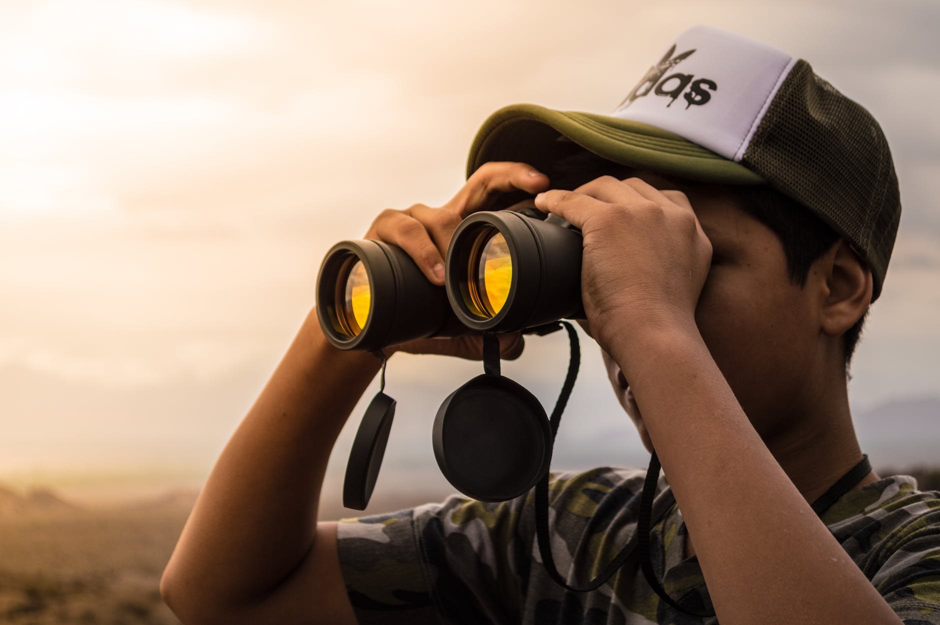 man looking in binoculars during sunset