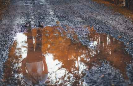 reflection photo of man standing on dirt road