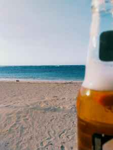 beverage bottle on seashore