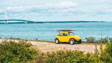 yellow volkswagen beetle on a seaside