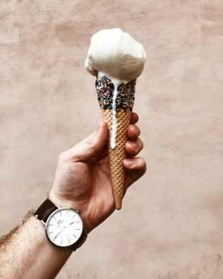 close up photo of man holding melting ice cream cone