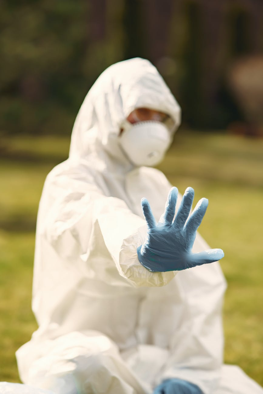 person in white protective suit sitting on green grass field